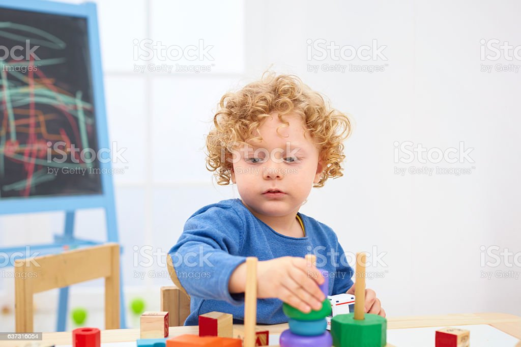 Little boy playing with wooden pyramid at table stock photo