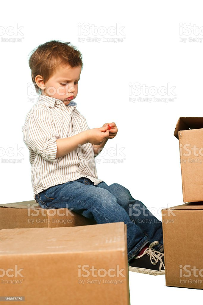 little boy plays in boxes stock photo