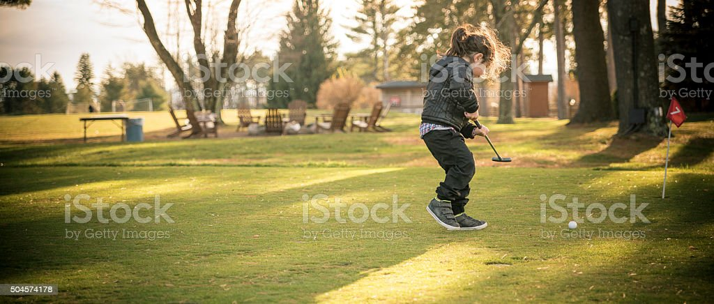 Little boy plays mini-golf at the lawn stock photo