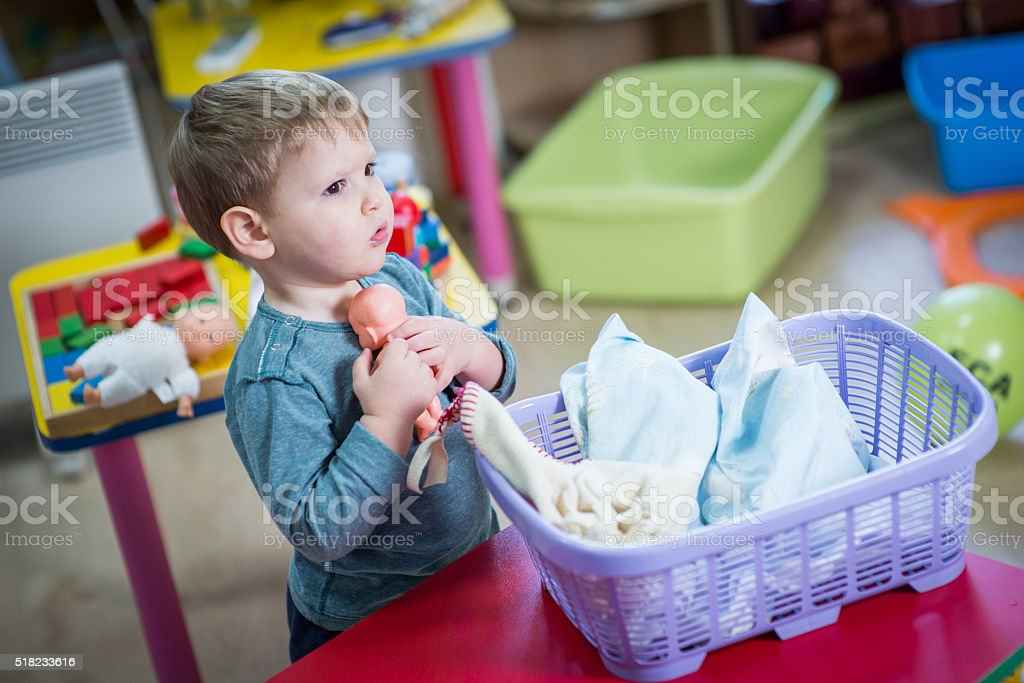 Little boy plays with a doll stock photo