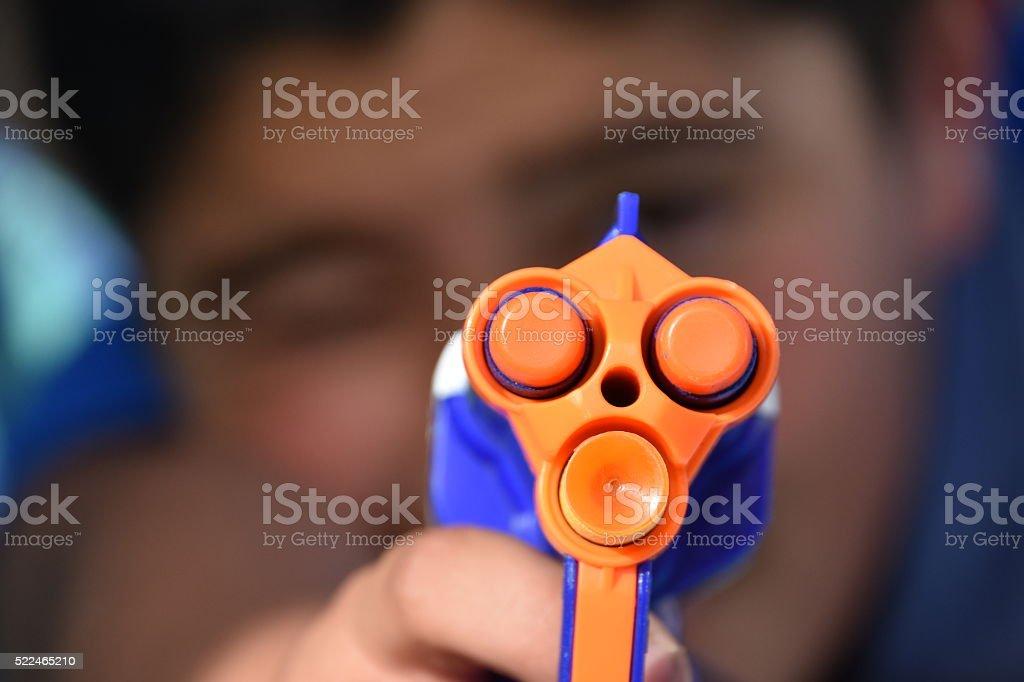 Little Boy Points His Toy Gun stock photo