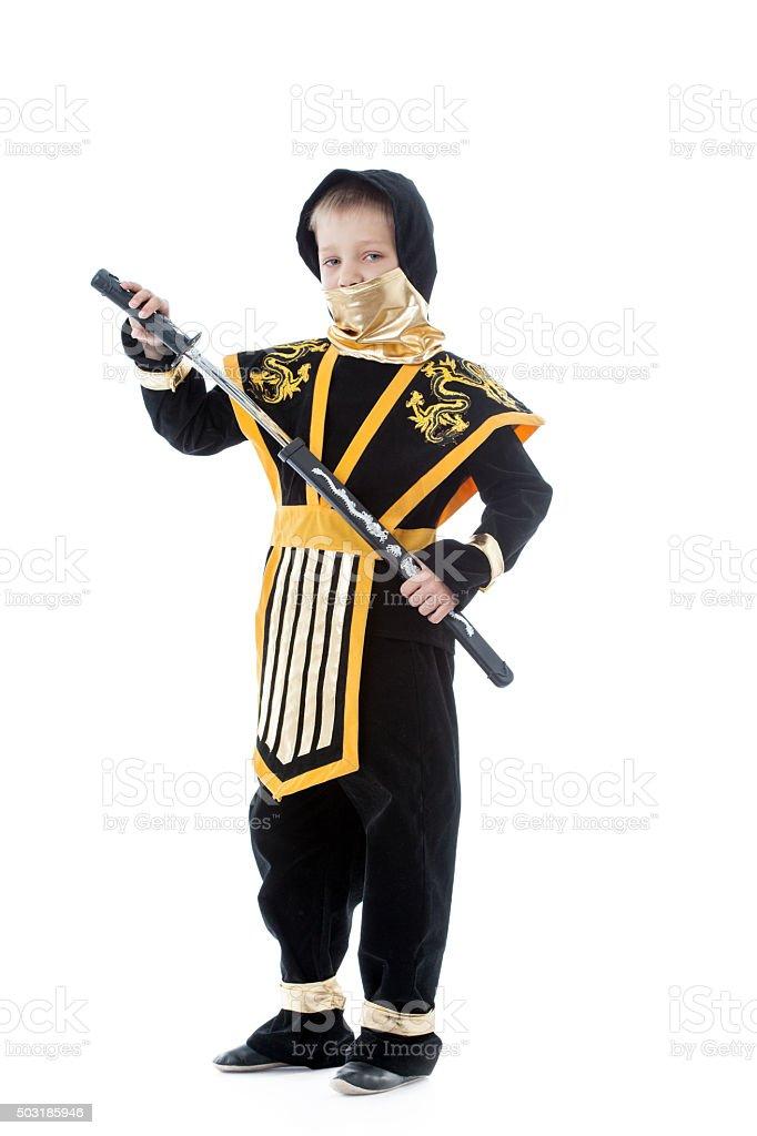 Little boy posing in ninja costume with katana stock photo