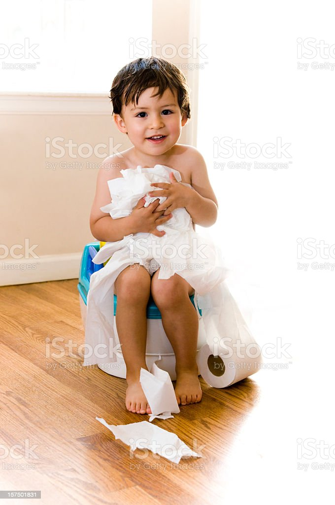 Little boy potty training with unrolled toilet paper royalty-free stock photo