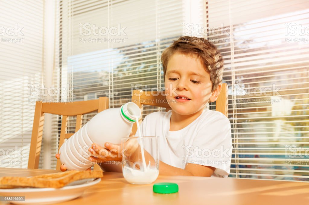 Little boy pouring milk to glass in the kitchen stock photo
