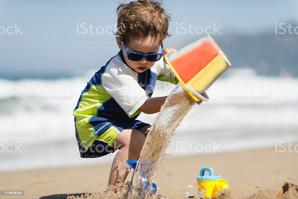 Little boy pouring water from bucket royalty-free stock photo