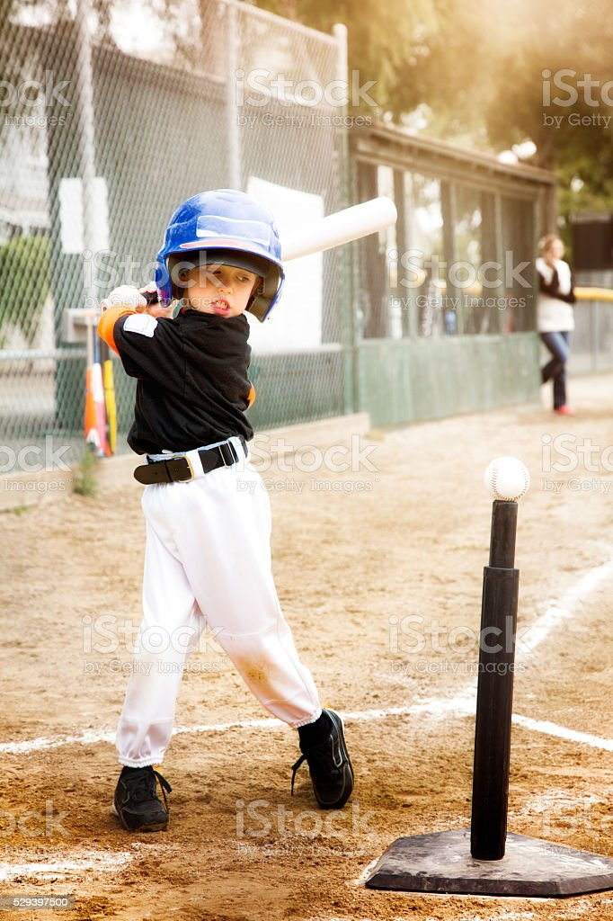 Little boy practicing baseball swing at T-Ball stock photo
