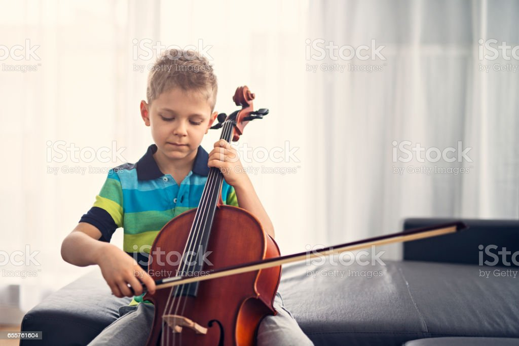 Little boy practicing cello at home stock photo