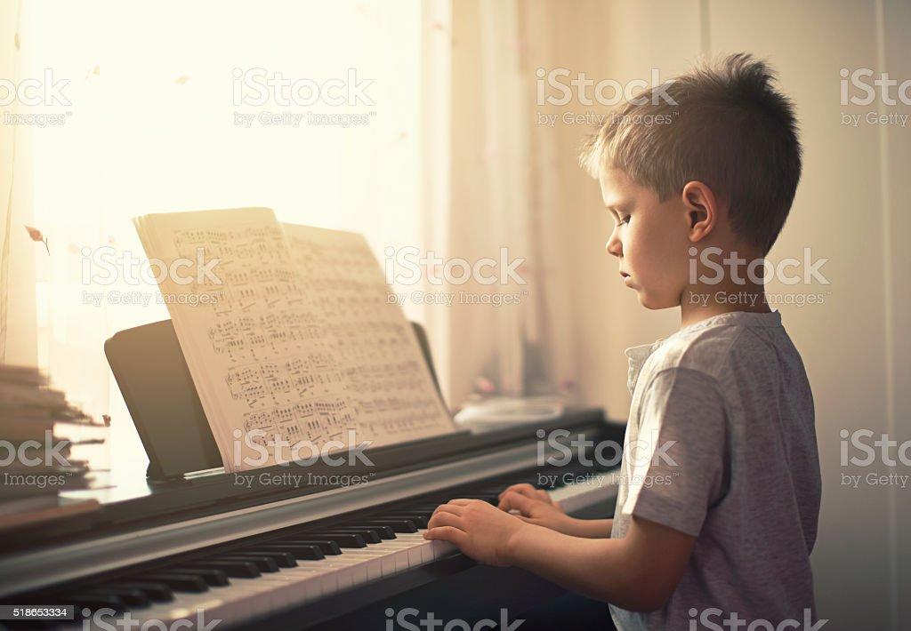 Little boy practicing digital piano. stock photo