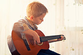 Little boy practicing guitar.