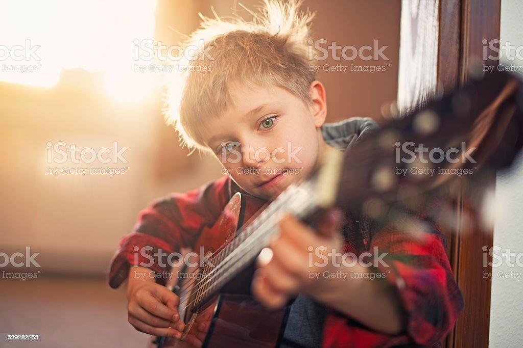 Little boy practicing guitar. stock photo
