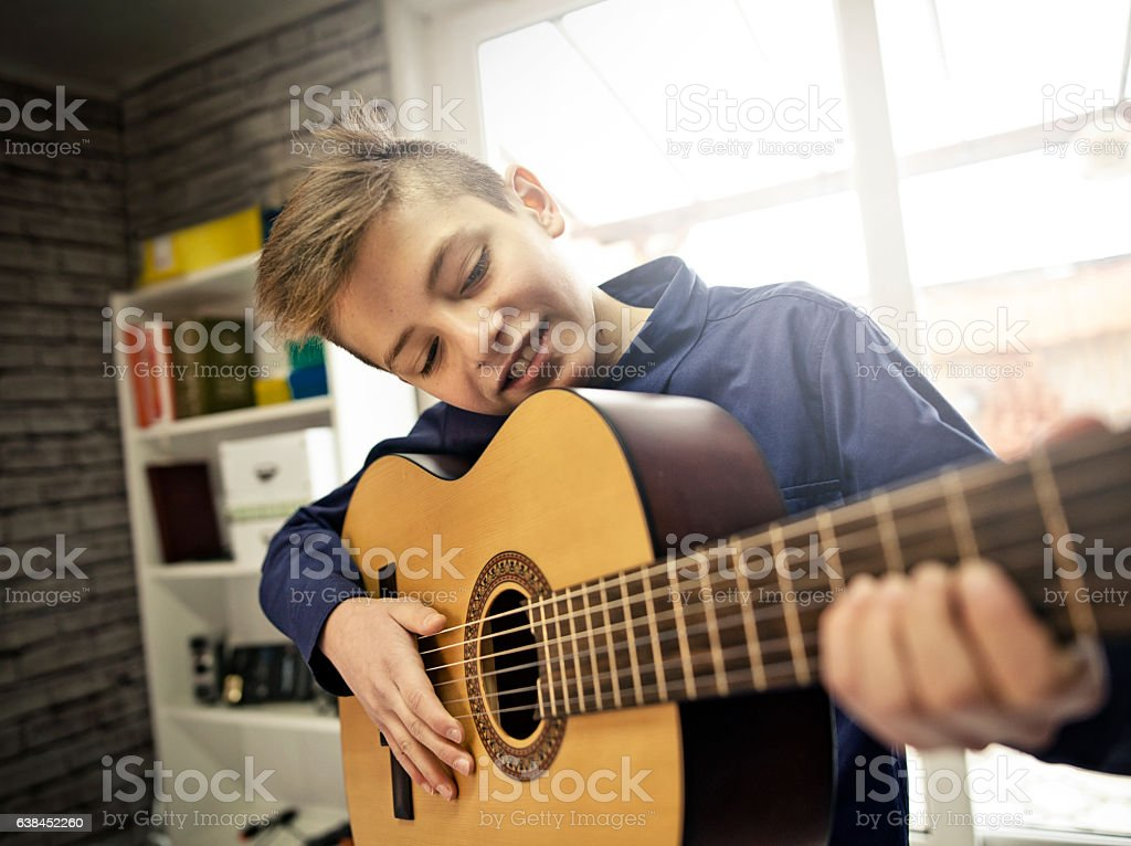 Little boy practicing guitar. stock photo