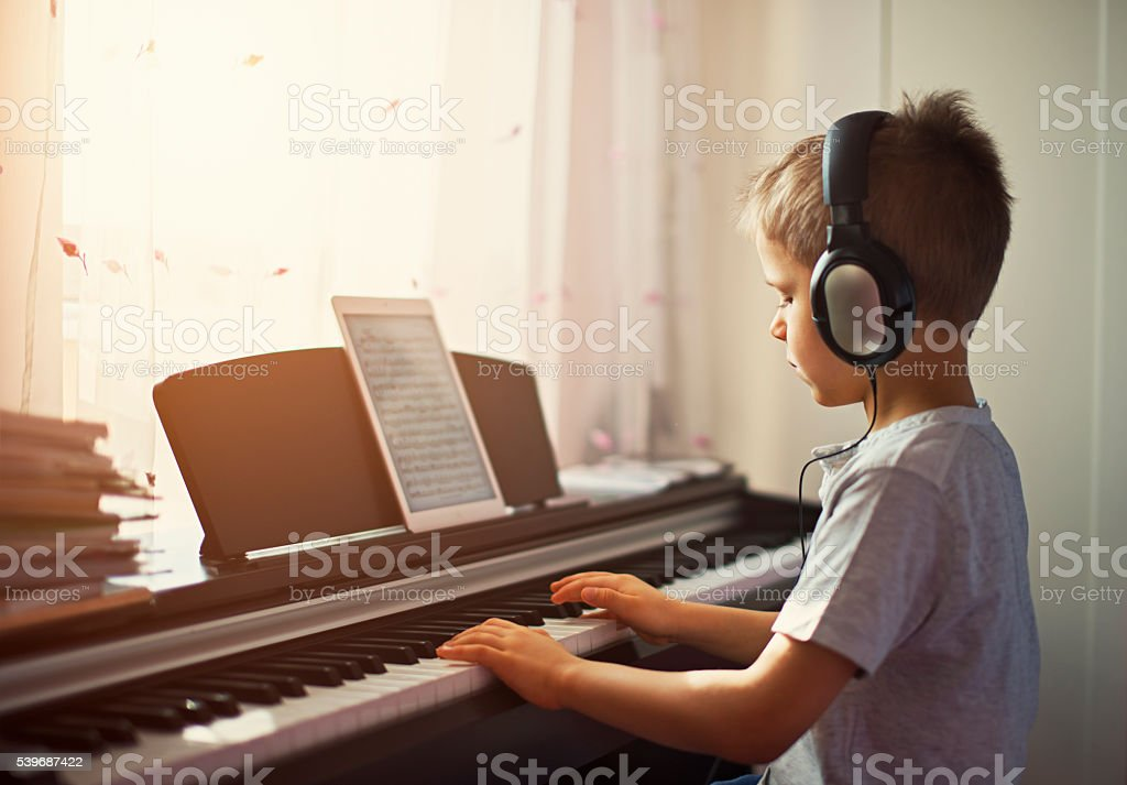 Little boy practicing modern digital piano. stock photo