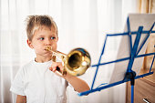 Little boy practicing playing trumpet