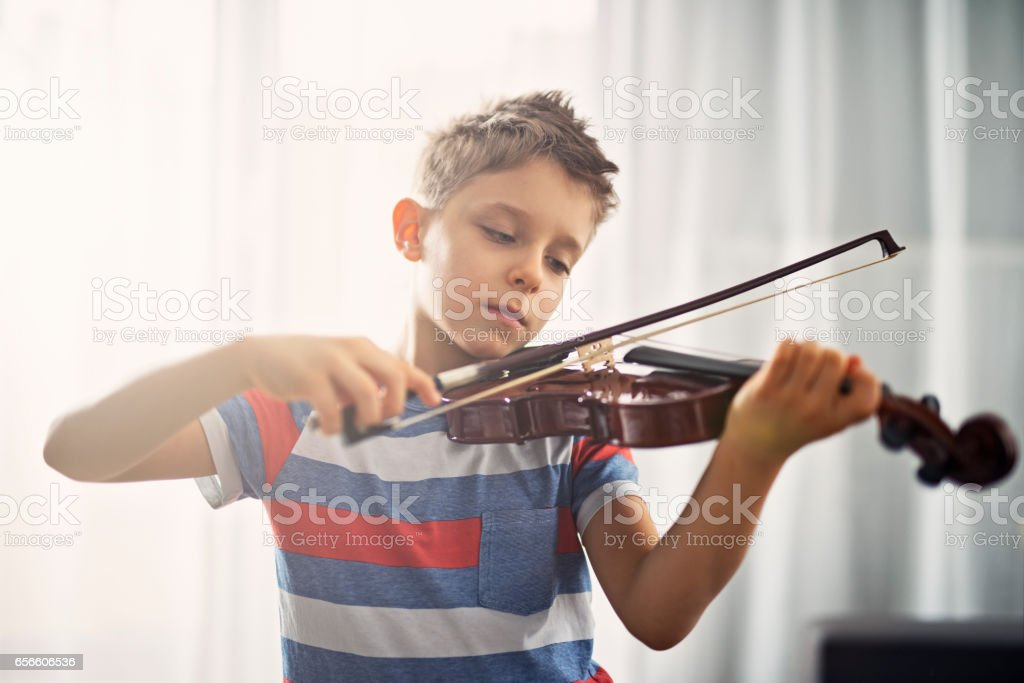 Little boy practicing violin at home stock photo