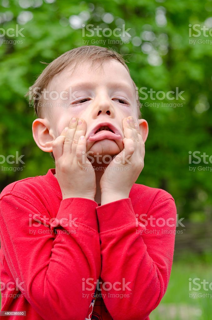 Little boy pulling a scary expression stock photo