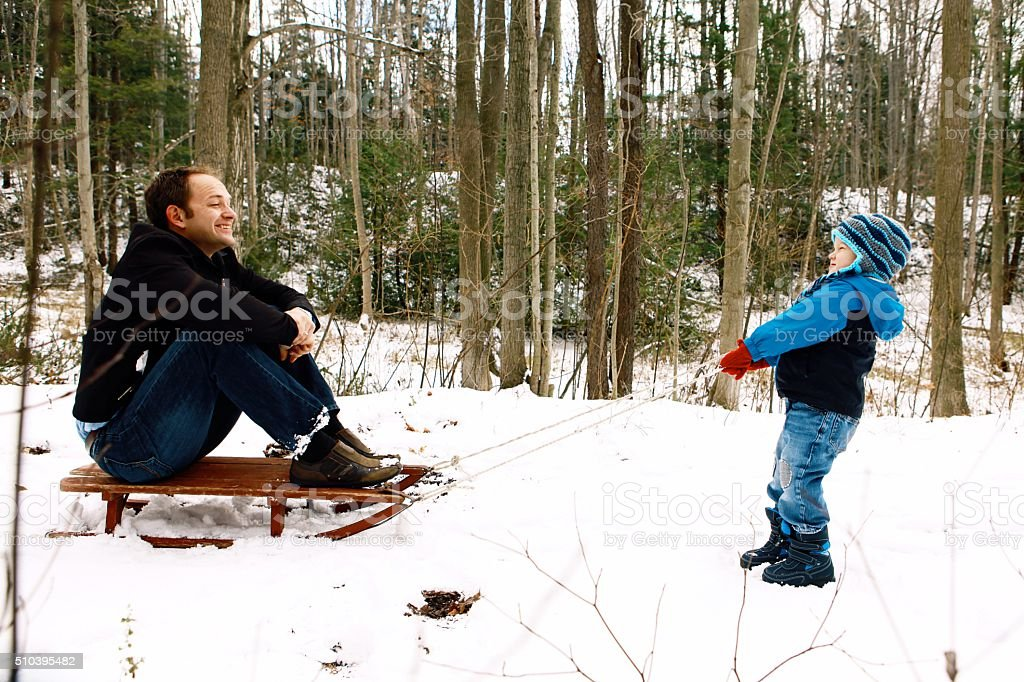 Little Boy Pulling Dad on Sled stock photo