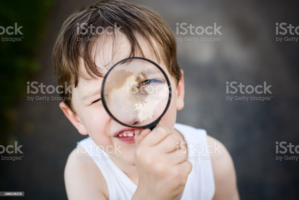 little boy puts a magnifying glass to eye stock photo