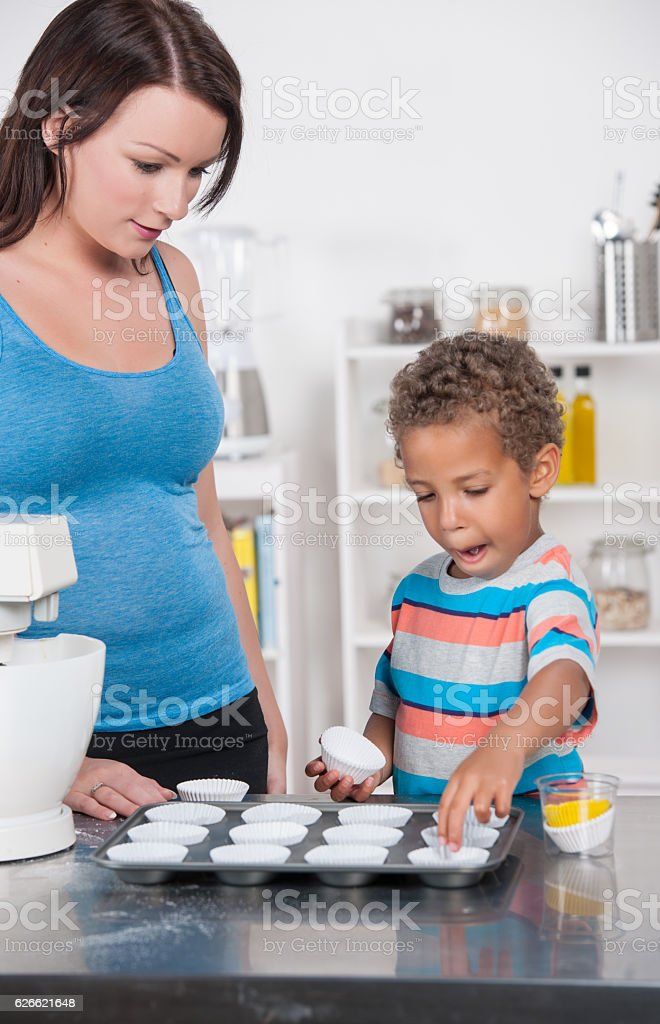 Little Boy Putting Cupcake Liners on a Baking Tray stock photo