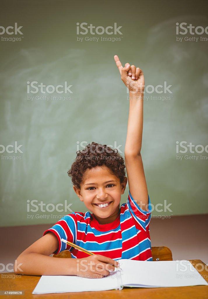 Little boy raising hand in classroom stock photo