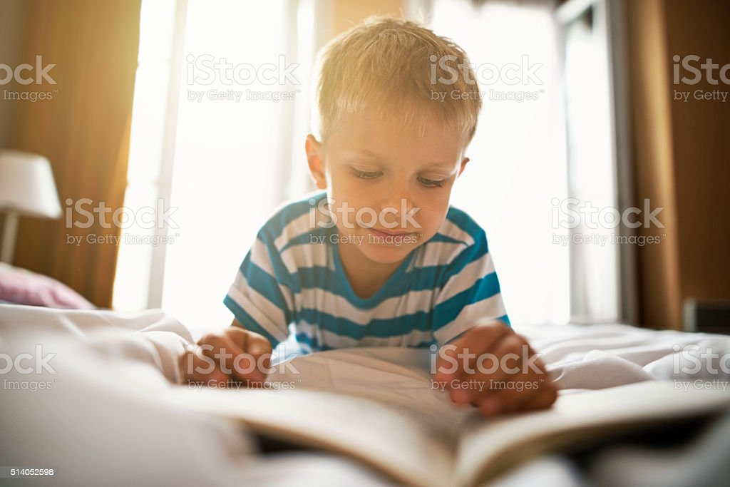 Little boy reading a book on bed. stock photo
