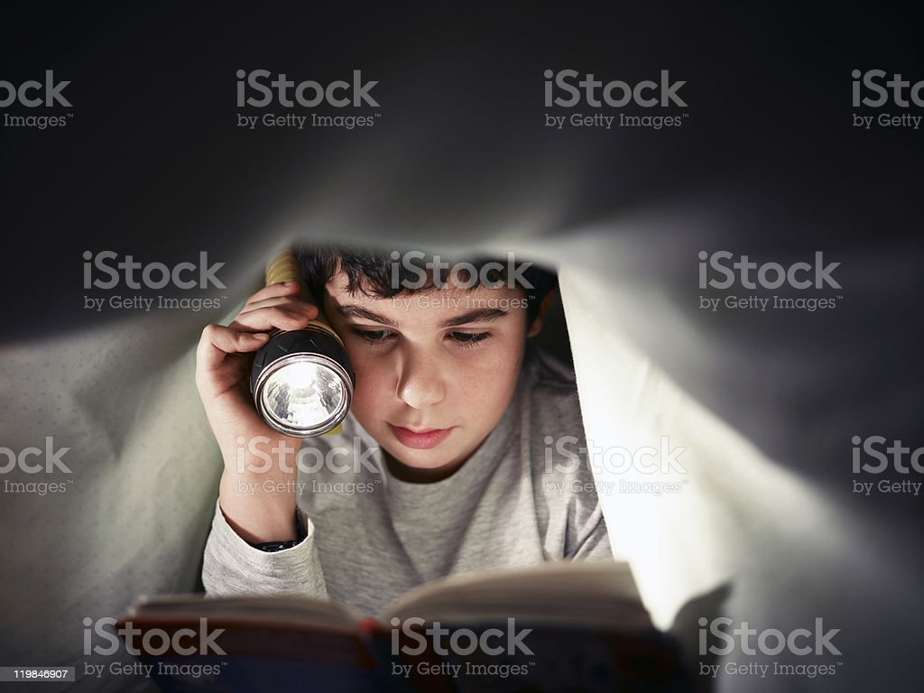 Little boy reading a book under the covers with flashlight stock photo