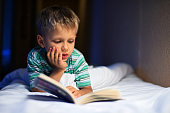Little boy reading book in bed