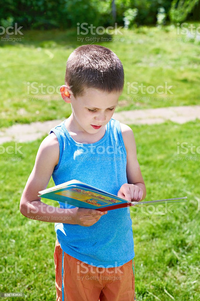 Little boy reading books outdoors stock photo