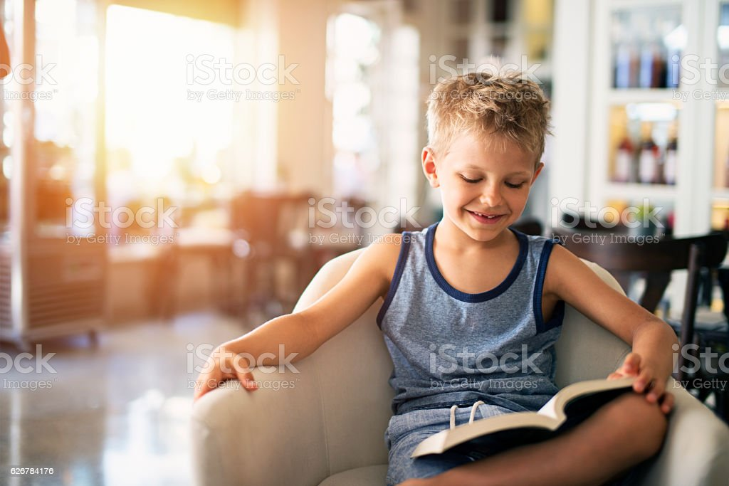 Little boy reading funny book in restaurant stock photo