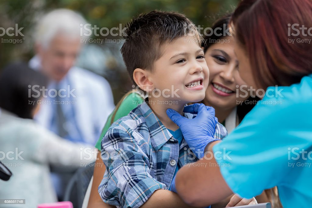 Little boy receives treatment at outdoor free clinic stock photo