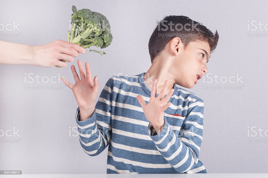 Little boy refusing to eat his vegetables stock photo
