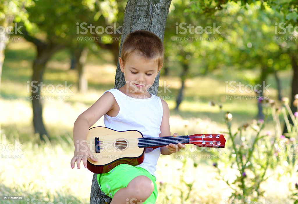 Little boy rehearsing on his acoustic guitar stock photo