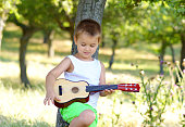 Little boy rehearsing on his acoustic guitar