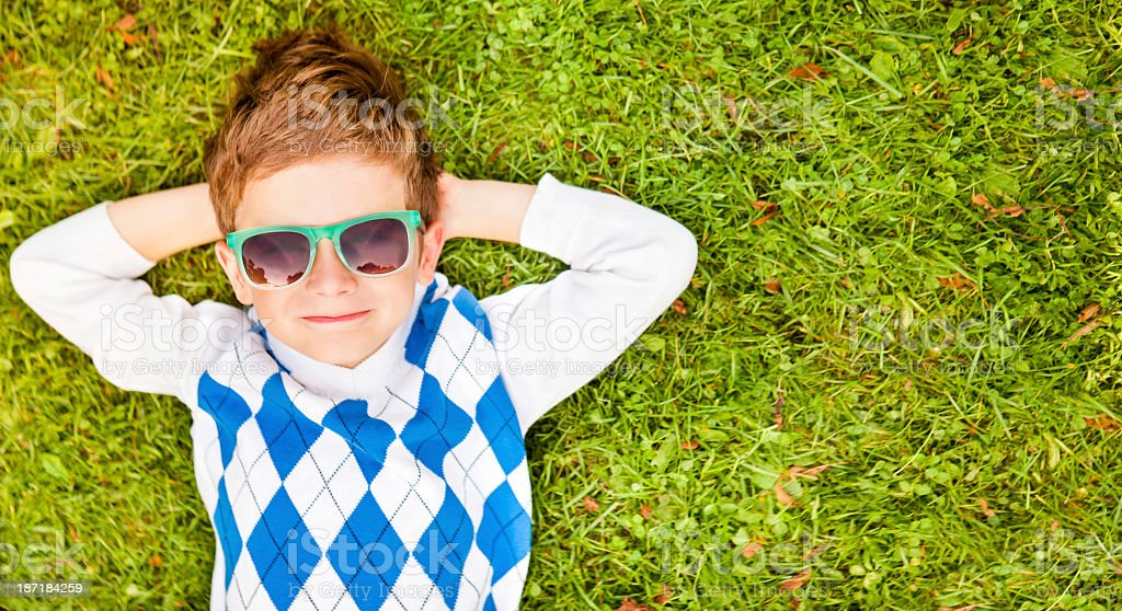 Little Boy Relaxing On Grass stock photo