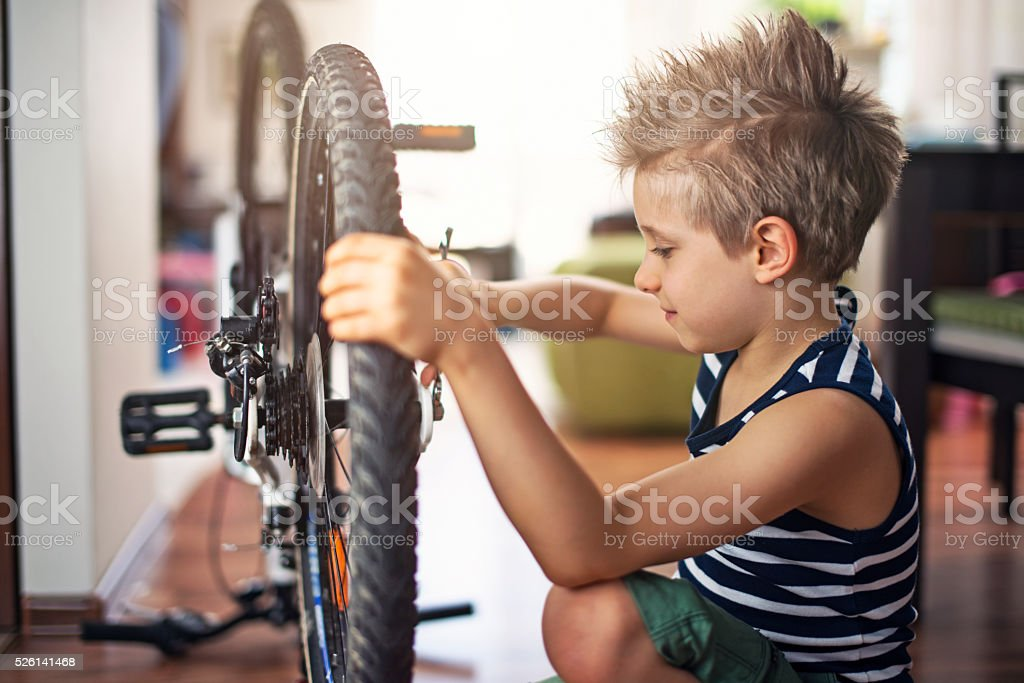 Little boy repairing a bicycle at home stock photo