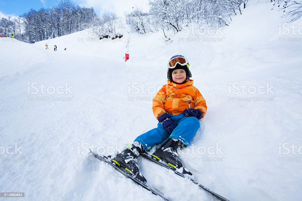 Little boy rest after ski lesson sitting in snow stock photo