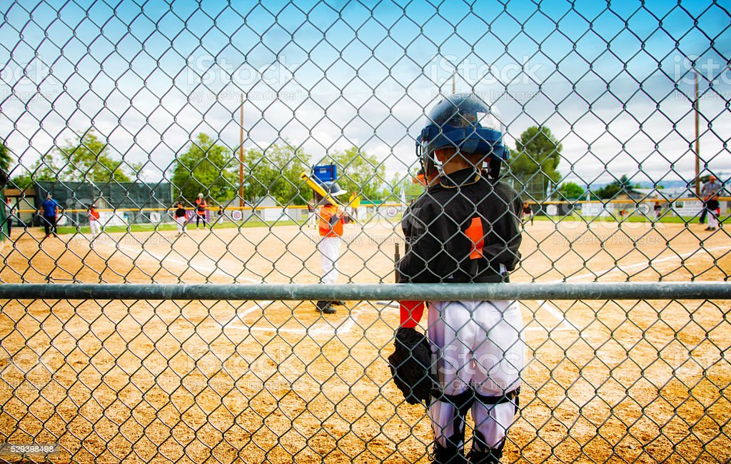 Little boy resting against fence during baseball game stock photo