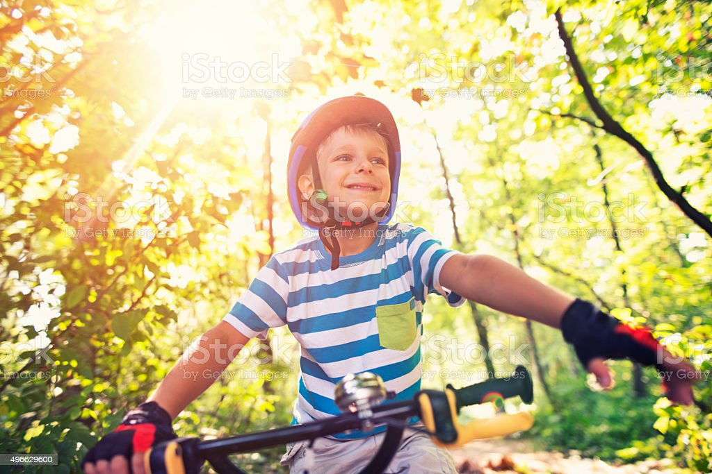 Little boy riding a bicycle in forest stock photo