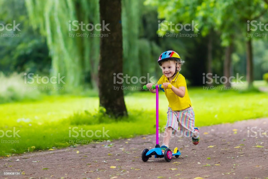 Little boy riding a colorful scooter stock photo