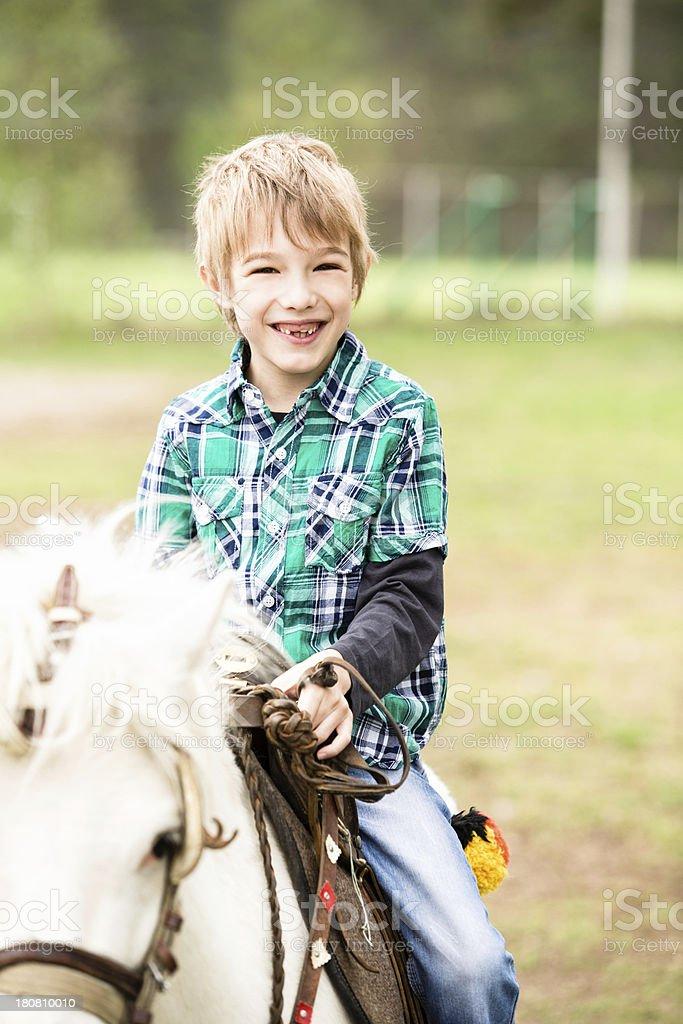 Little boy riding a horse royalty-free stock photo