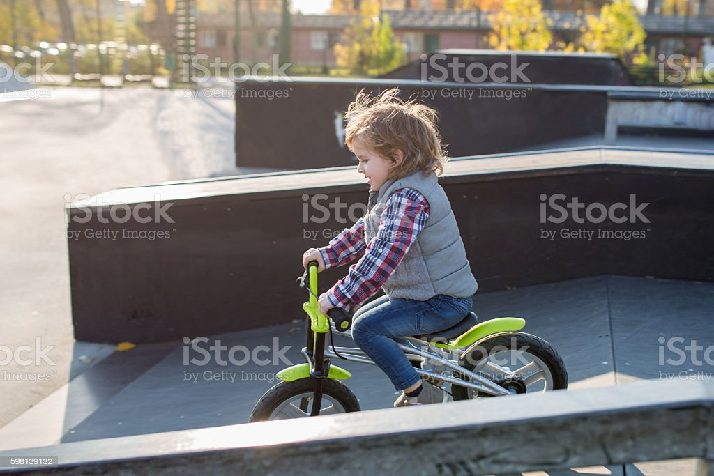 Little boy riding bicycle in skateboard park. stock photo