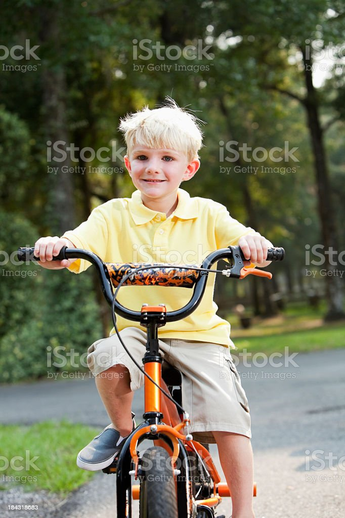 Little boy riding bicycle stock photo