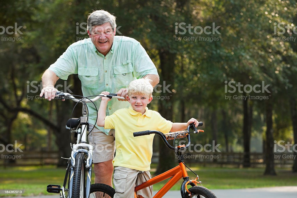 Little boy riding bike with grandfather stock photo