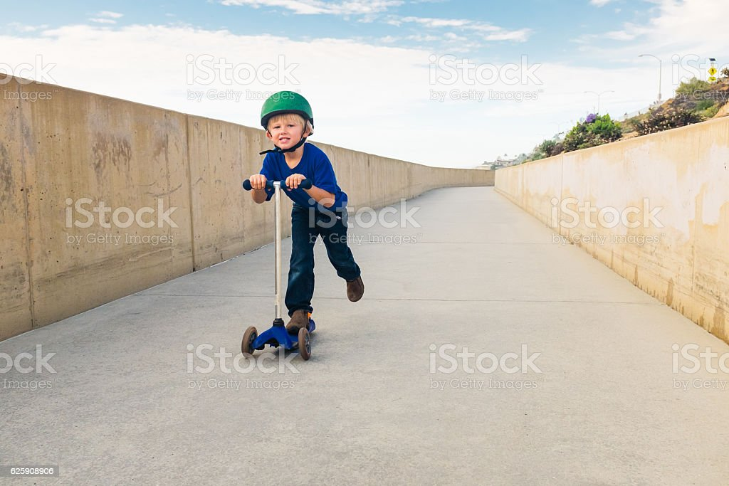 Little Boy Riding His Scooter Down A Bike Path stock photo
