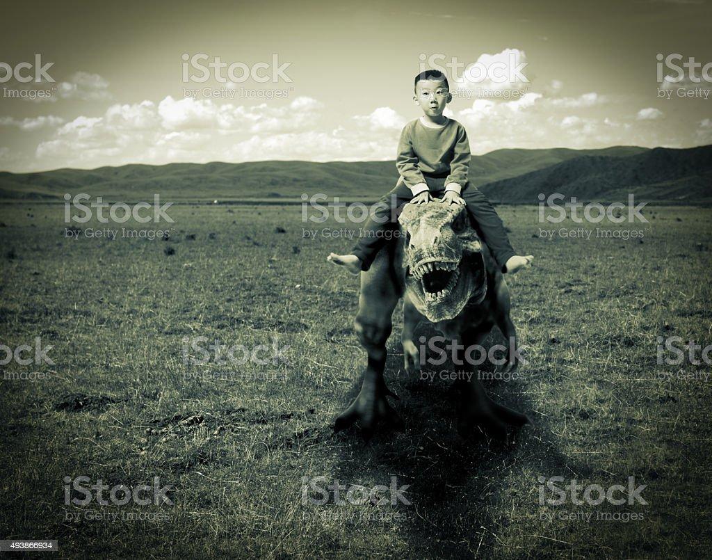 little boy  riding on dinosaur stock photo