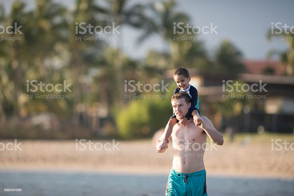 Little Boy Riding on His Father's Shoulders stock photo