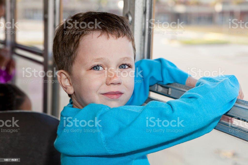 Little boy riding school bus stock photo