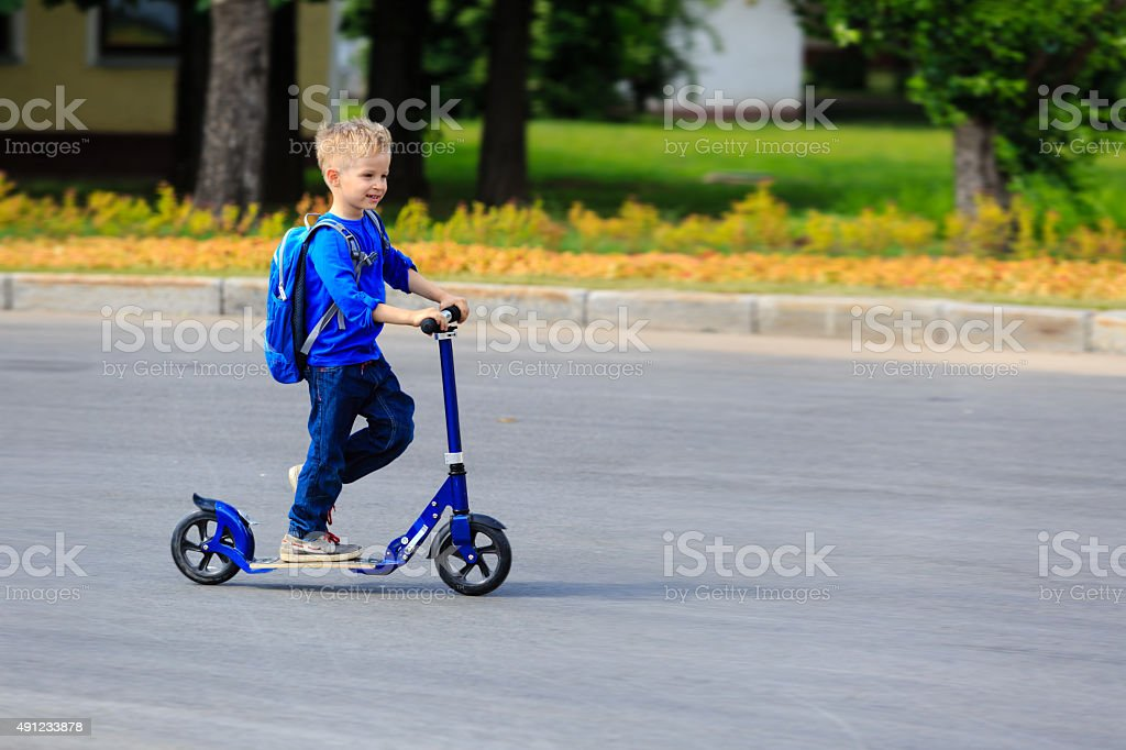 little boy riding scooter in the city stock photo