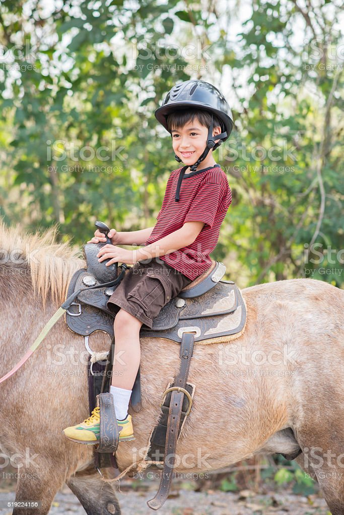 Little boy riding training horse stock photo