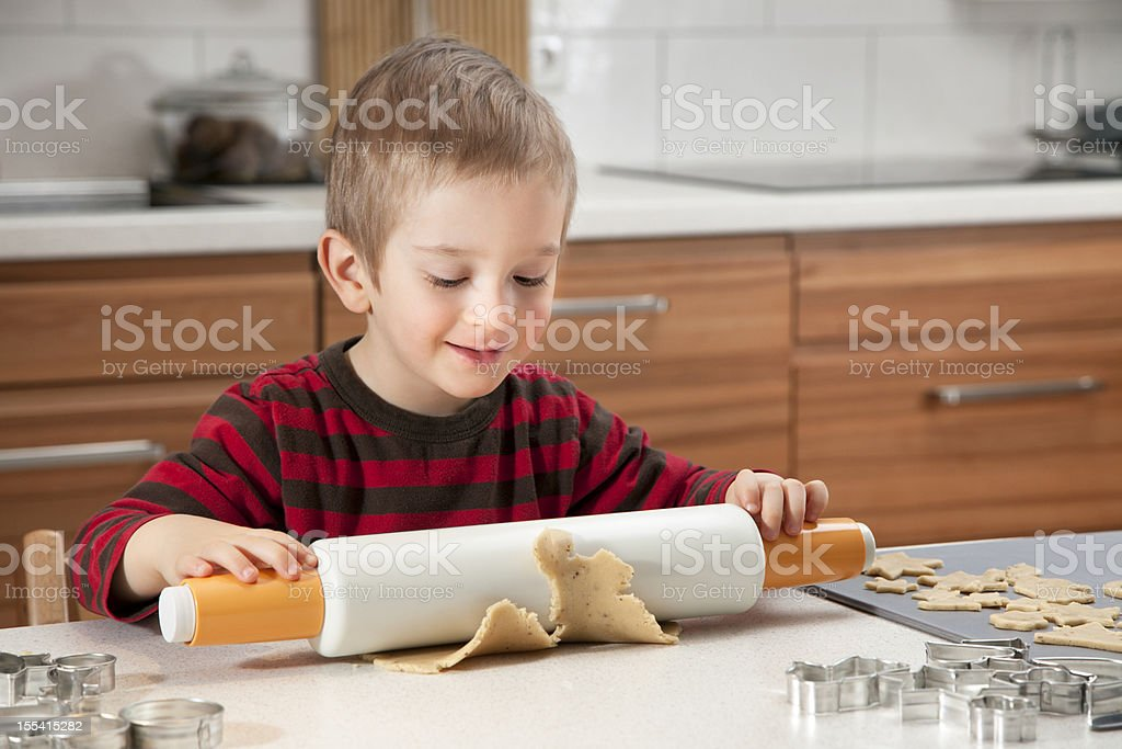 Little Boy Rolling Out Cookie Dough In Kitchen stock photo
