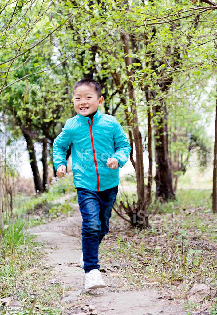 Little boy running in forest stock photo